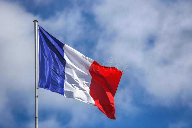 Drapeau français contre le ciel nuageux bleu photographie stock libre de droits