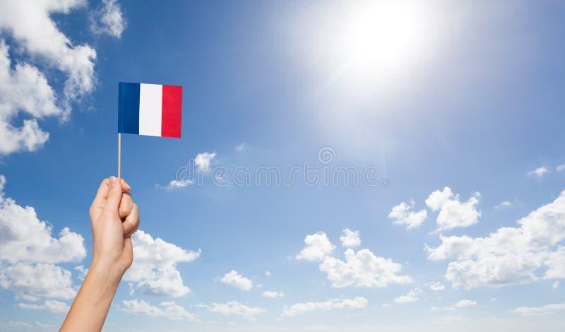 Drapeau français de participation de la main de la femme au-dessus du mât de drapeau image libre de droits