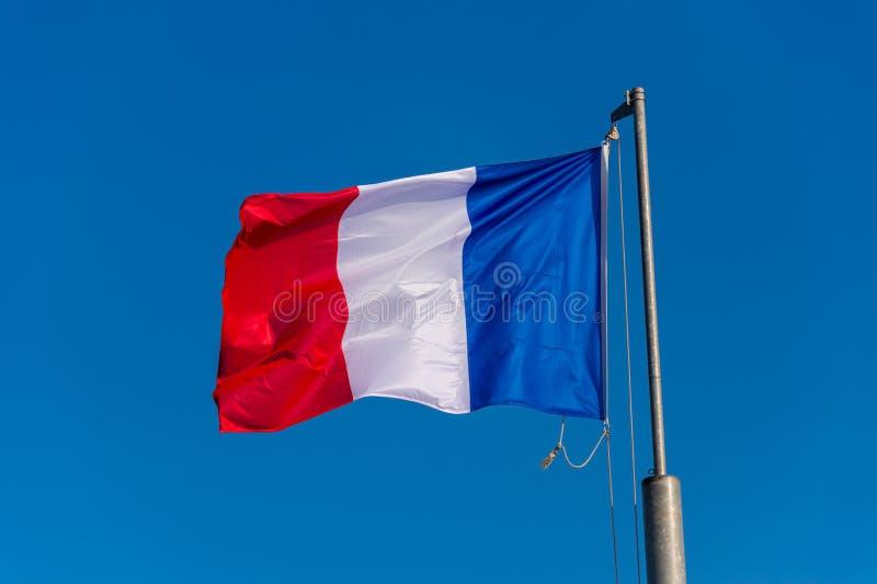 Drapeau français ondulant contre le ciel bleu images stock
