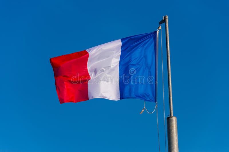 Drapeau français ondulant contre le ciel bleu image libre de droits