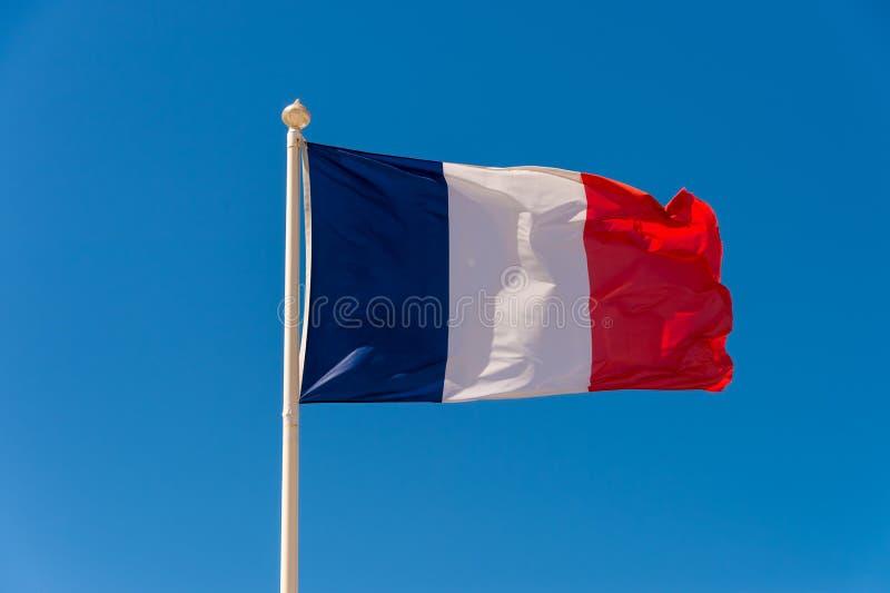 Drapeau français ondulant contre le ciel bleu photo stock