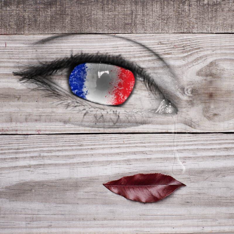 Drapeau français sur l'élève d'oeil avec la baisse de larme, lèvres réalistes sur le fond gris en bois photo stock