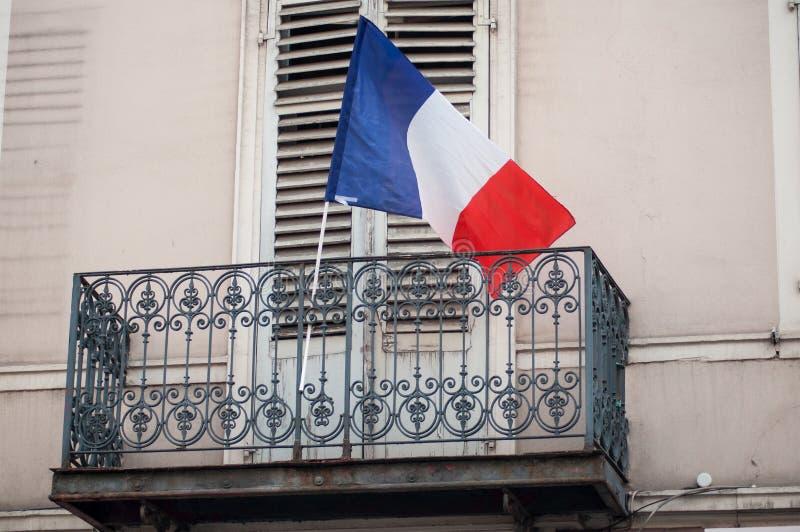 Drapeau français sur le balcon de la façade de bâtiment photographie stock libre de droits