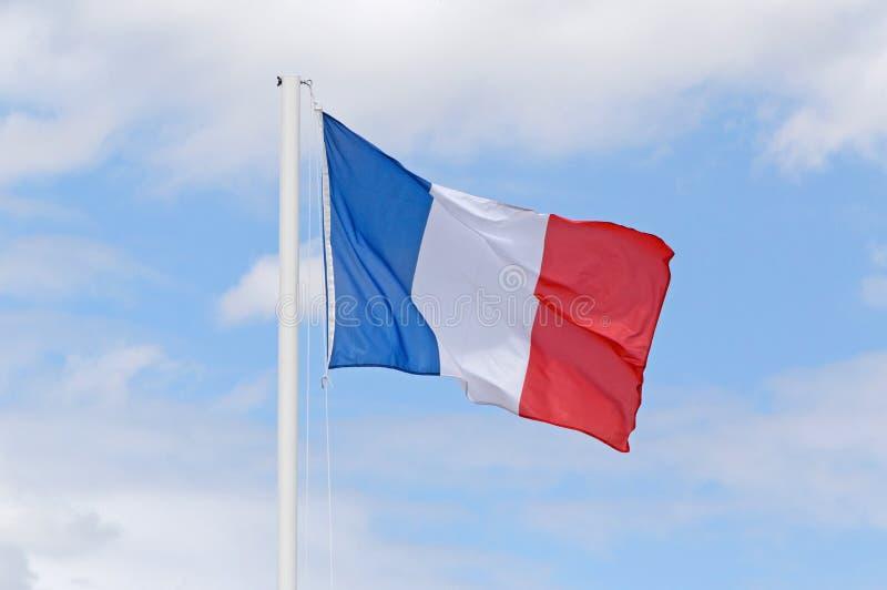 Drapeau français sur le mât de drapeau contre le ciel bleu image stock