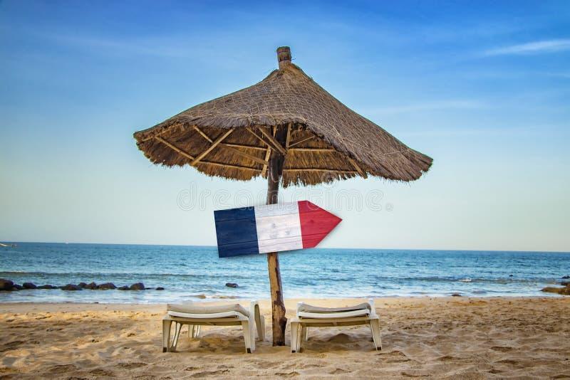Drapeau français sur le signe en bois de flèche Il y a deux canapés du soleil et un parapluie de soleil sur la plage C'est un par photo libre de droits