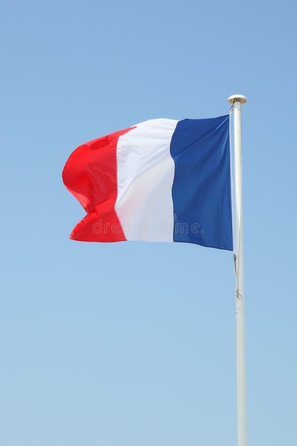 Drapeau français sur un tapis dans le vent et le ciel bleu photos stock