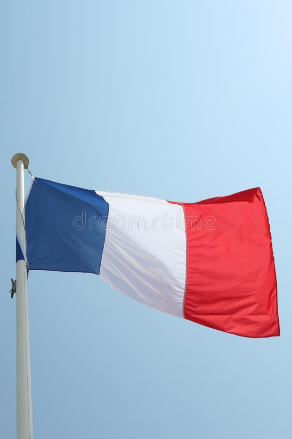 Drapeau français sur un tapis dans le vent et le ciel bleu photo stock