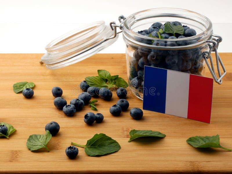 Drapeau français sur une planche en bois avec des myrtilles sur le blanc images stock