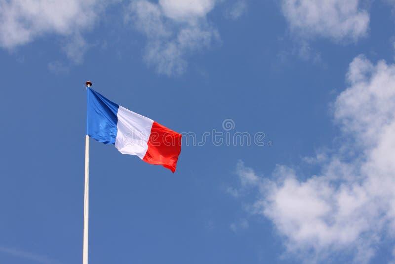 Drapeau français Tricolore ondulant d'un mât de drapeau avec le fond de ciel bleu Copiez l'espace pour écrire votre propre texte images stock