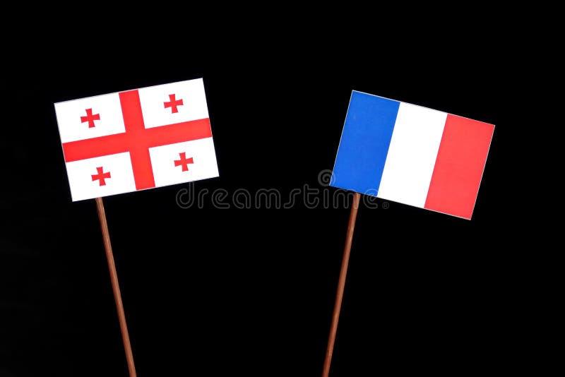 Drapeau géorgien avec le drapeau français d'isolement sur le noir photo stock