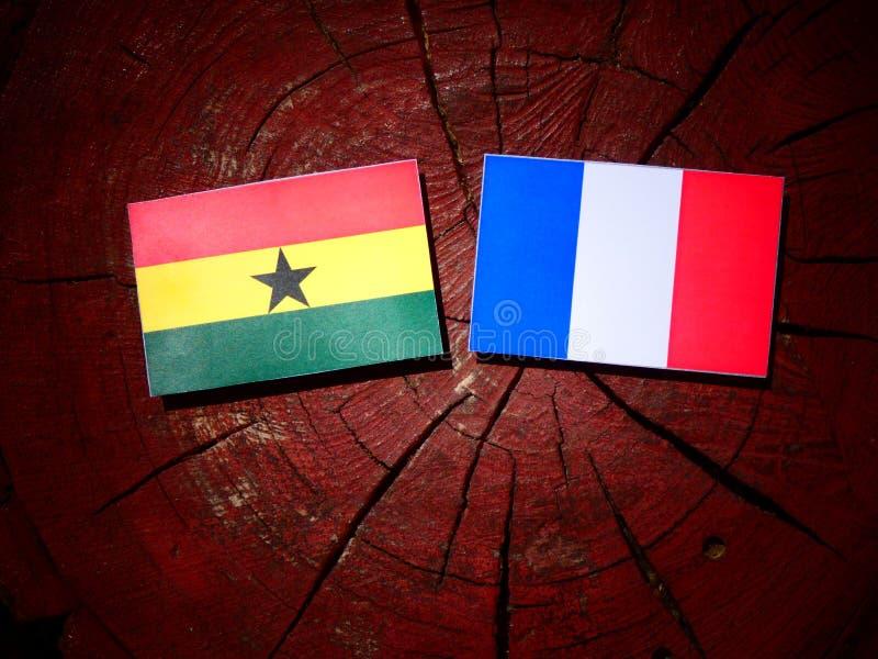 Drapeau ghanéen avec le drapeau français sur un tronçon d'arbre d'isolement image libre de droits