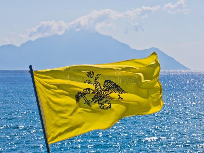 Drapeau grec de marine sur un bateau qui navigue près de la côte grecque de la mer Égée avec la montagne sainte Athos à l'arrière image libre de droits