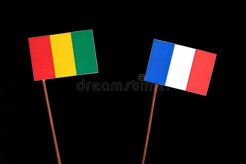 Drapeau guinéen avec le drapeau français d'isolement sur le noir photographie stock libre de droits