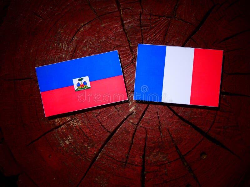 Drapeau haïtien avec le drapeau français sur un tronçon d'arbre d'isolement images stock