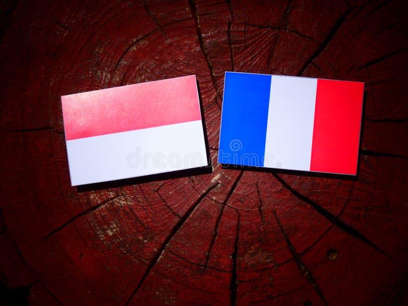 Drapeau indonésien avec le drapeau français sur un tronçon d'arbre d'isolement image libre de droits