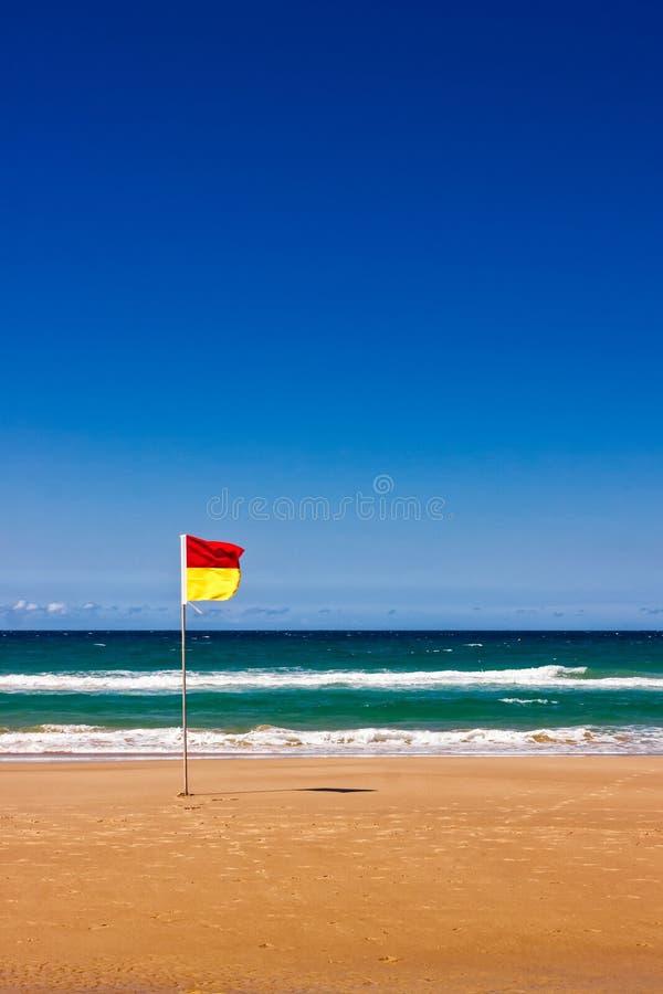 Drapeau isolé de maître nageur sur la plage australienne images stock