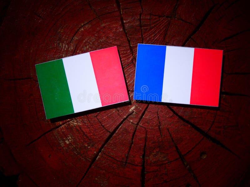 Drapeau italien avec le drapeau français sur un tronçon d'arbre d'isolement photographie stock libre de droits