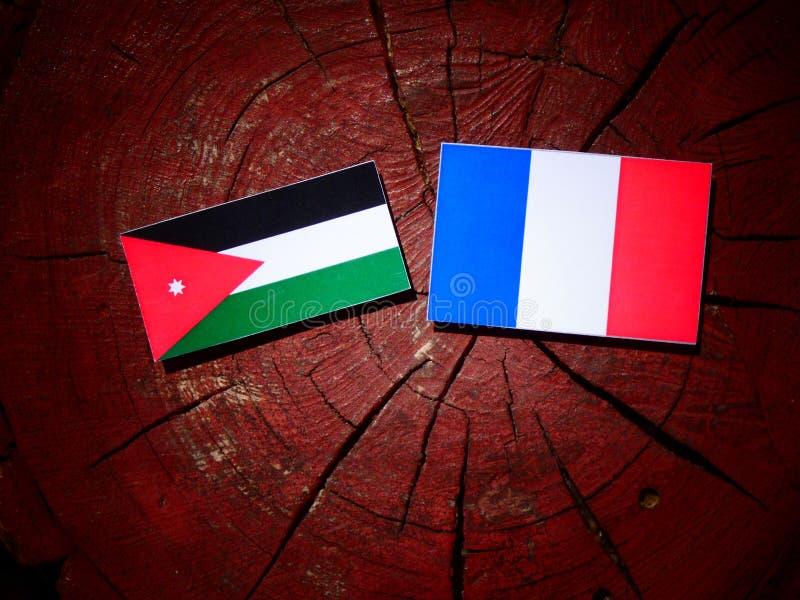 Drapeau jordanien avec le drapeau français sur un tronçon d'arbre d'isolement photographie stock libre de droits