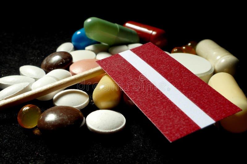 Drapeau letton avec le sort de pilules médicales d'isolement sur le fond noir images libres de droits
