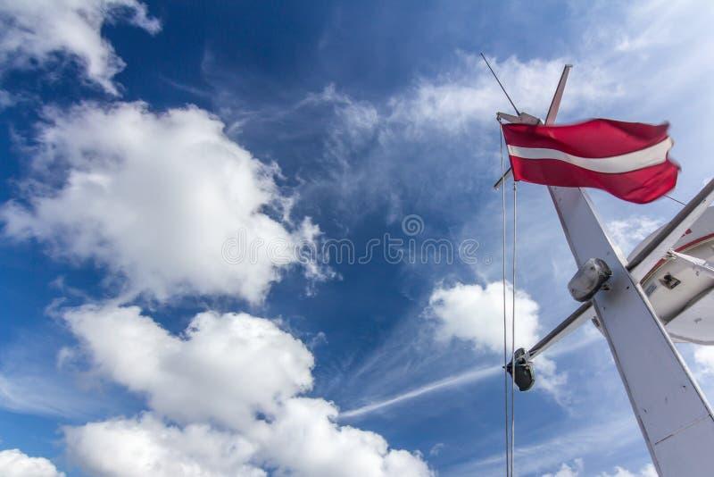 Drapeau letton sur le mât de bateau avec de grands grands nuages blancs photographie stock libre de droits