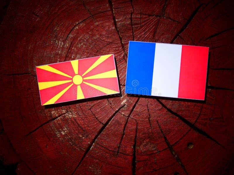 Drapeau macédonien avec le drapeau français sur un tronçon d'arbre d'isolement photo stock