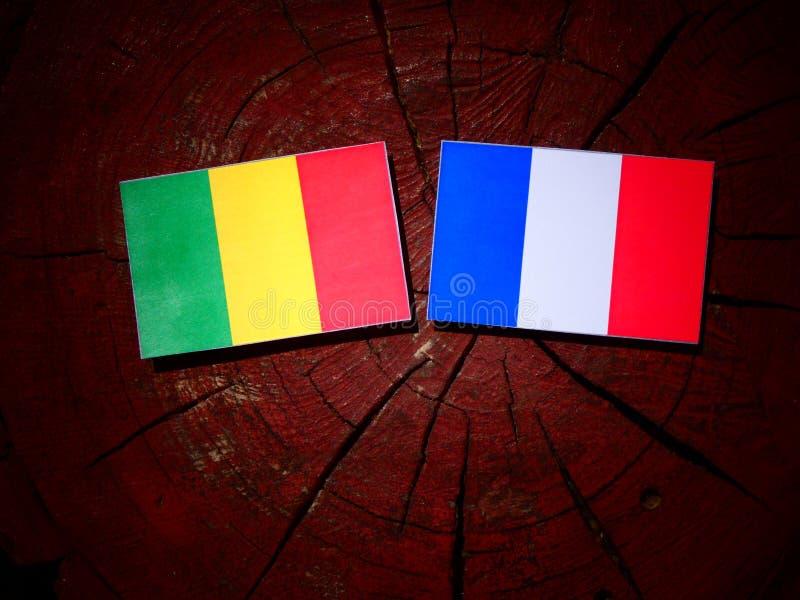 Drapeau malien avec le drapeau français sur un tronçon d'arbre d'isolement images stock