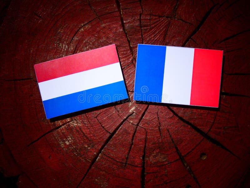 Drapeau néerlandais avec le drapeau français sur un tronçon d'arbre d'isolement image stock