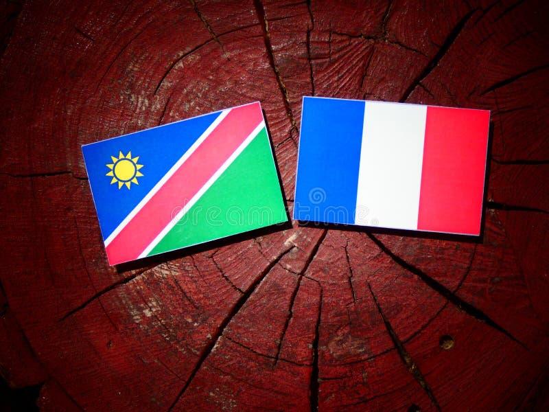 Drapeau namibien avec le drapeau français sur un tronçon d'arbre d'isolement photo stock