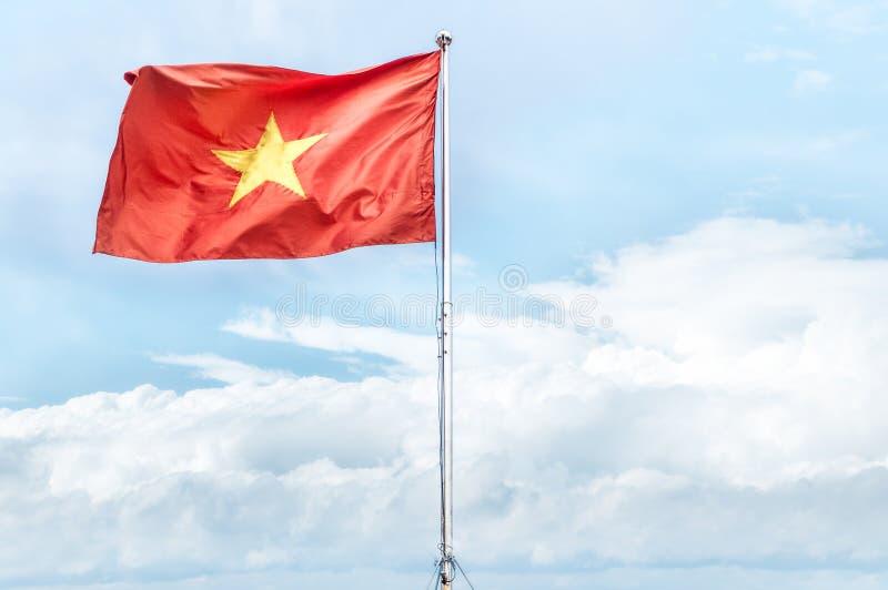 Drapeau national rouge du Vietnam ondulant en ciel bleu. images libres de droits