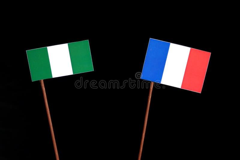 Drapeau nigérien avec le drapeau français sur le noir images stock