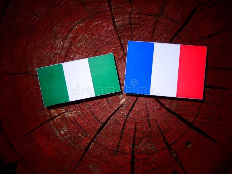 Drapeau nigérien avec le drapeau français sur un tronçon d'arbre d'isolement photographie stock libre de droits