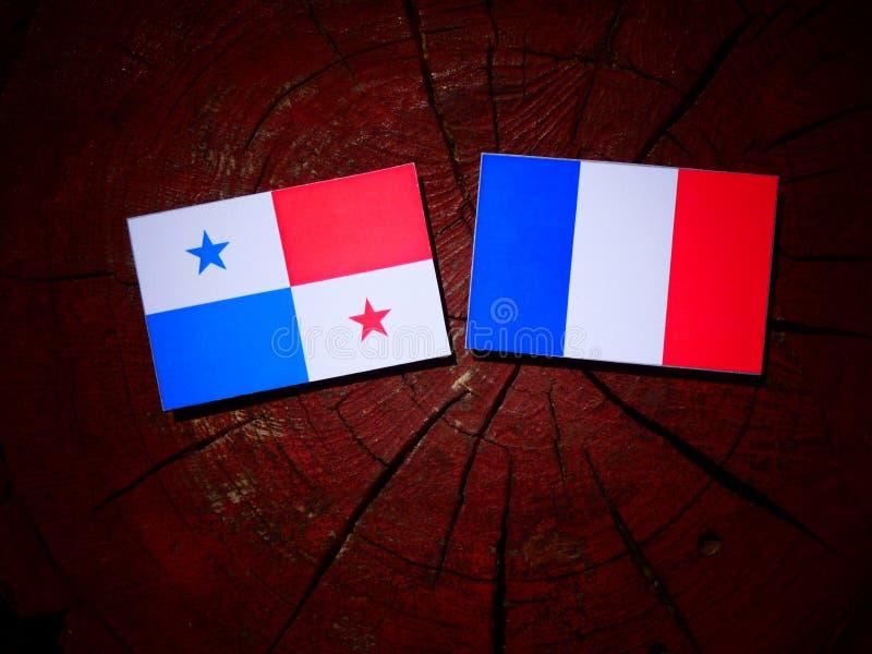 Drapeau panaméen avec le drapeau français sur un tronçon d'arbre d'isolement photos stock