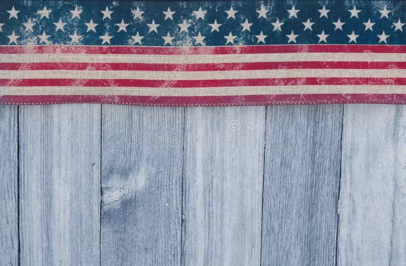 Drapeau patriotique des Etats-Unis vieux sur un fond en bois superficiel par les agents photo stock
