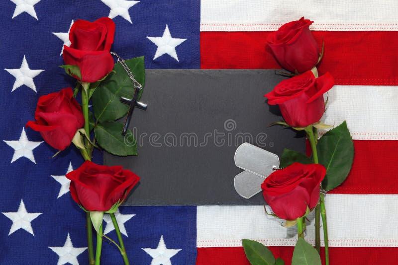Drapeau am?ricain avec des roses et des ?tiquettes de chien militaires photographie stock