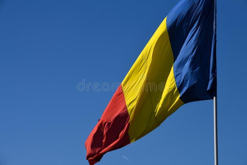 Drapeau roumain dans le vent un jour ensoleillé avec le ciel bleu clair photos stock