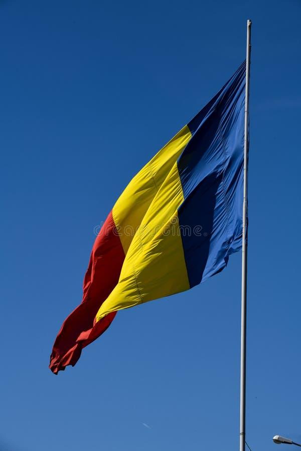 Drapeau roumain dans le vent un jour ensoleillé avec le ciel bleu clair photos libres de droits