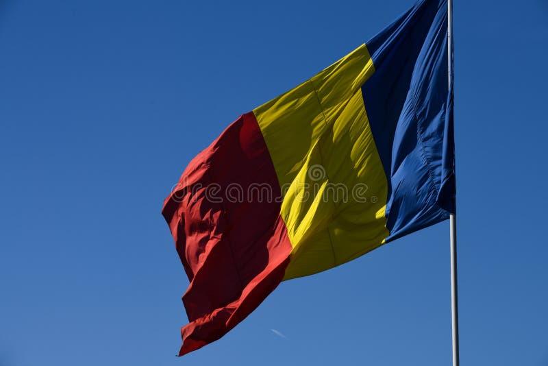 Drapeau roumain dans le vent un jour ensoleillé avec le ciel bleu clair image libre de droits