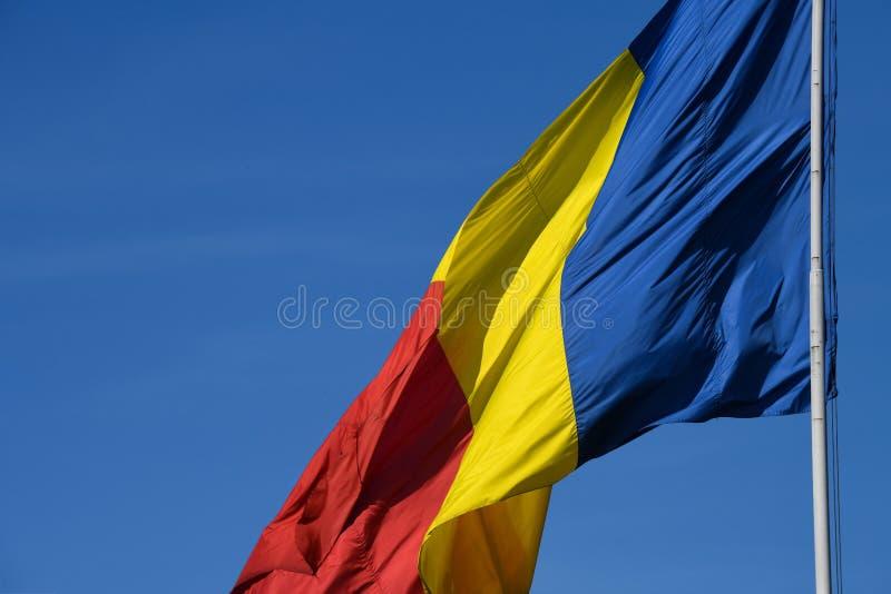 Drapeau roumain dans le vent un jour ensoleillé avec le ciel bleu clair images stock