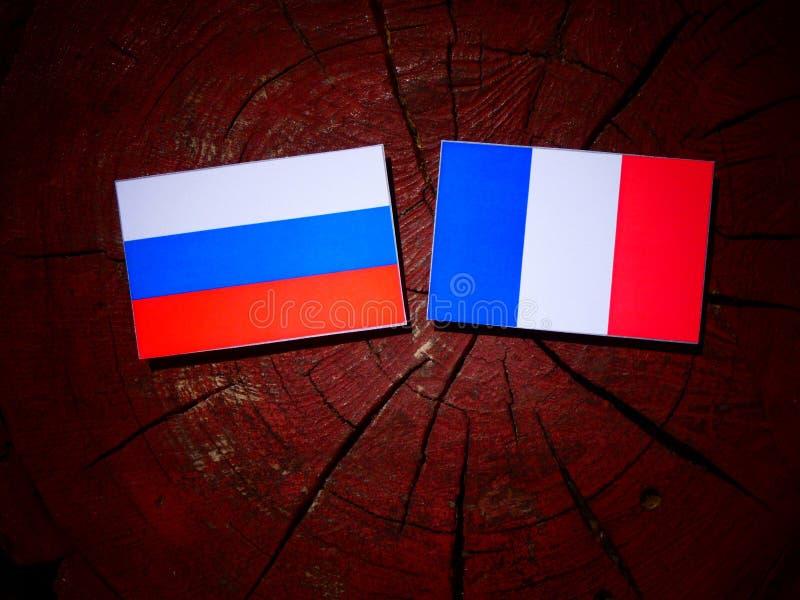 Drapeau russe avec le drapeau français sur un tronçon d'arbre d'isolement photographie stock libre de droits