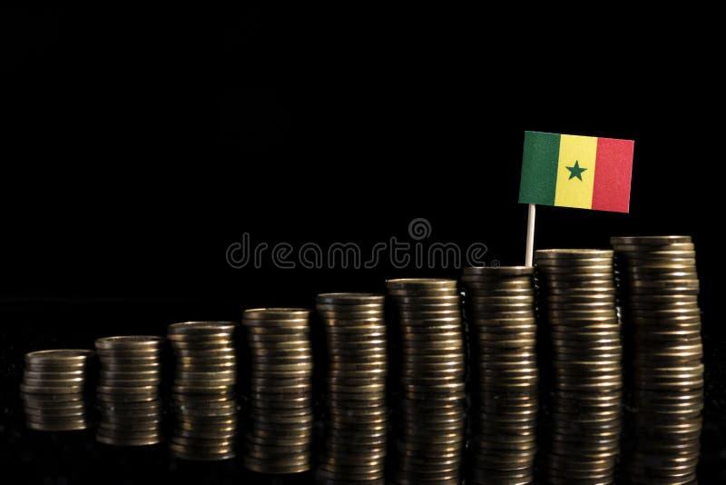 Drapeau sénégalais avec le sort de pièces de monnaie sur le noir photos stock
