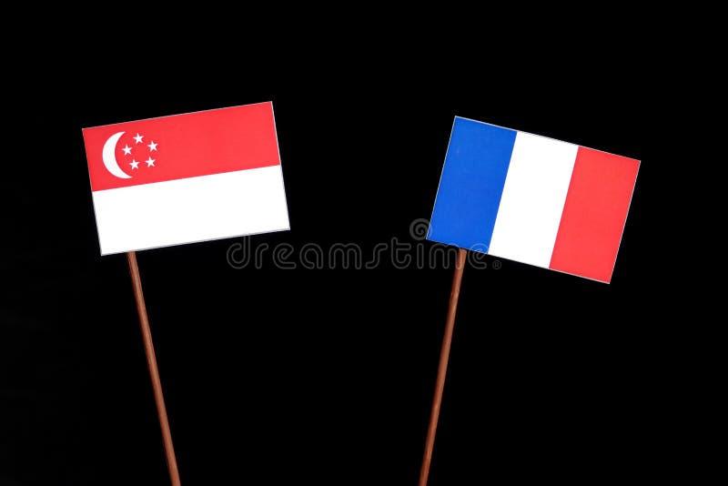 Drapeau singapourien avec le drapeau français sur le noir photos stock