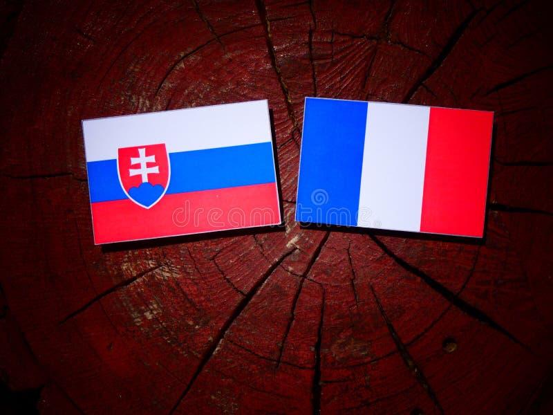 Drapeau slovaque avec le drapeau français sur un tronçon d'arbre d'isolement images libres de droits