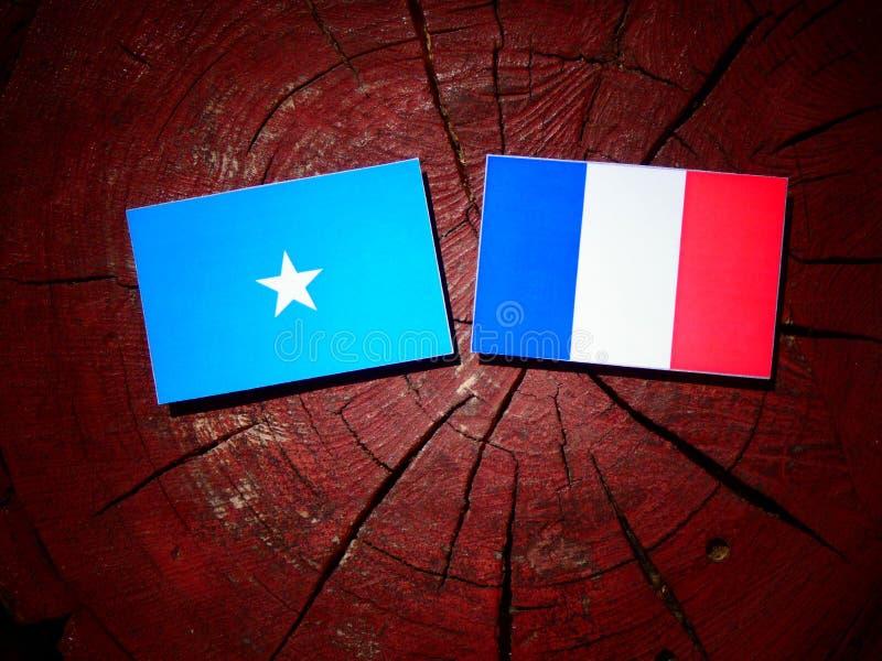 Drapeau somalien avec le drapeau français sur un tronçon d'arbre d'isolement photo libre de droits