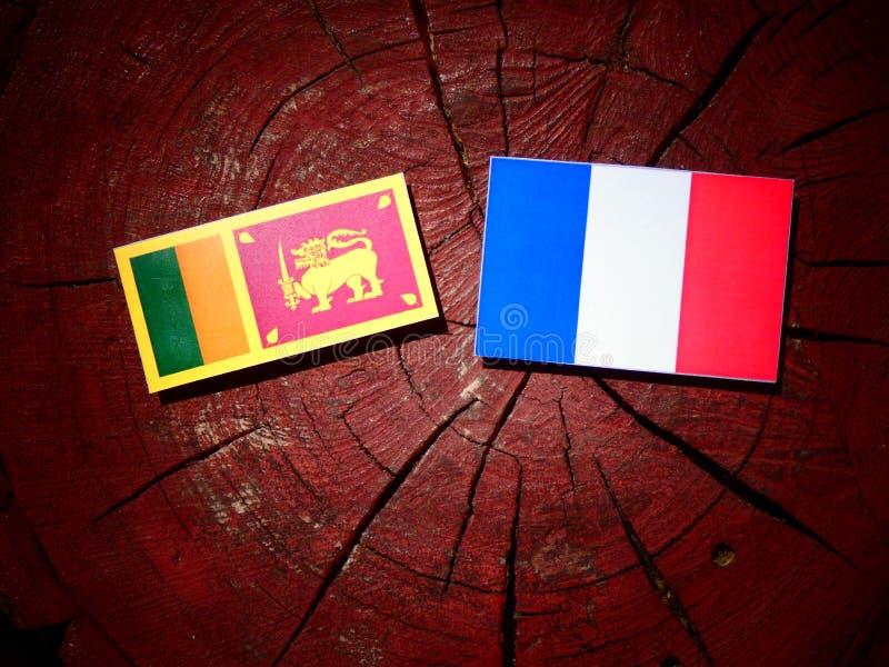 Drapeau sri-lankais avec le drapeau français sur un tronçon d'arbre d'isolement photos stock
