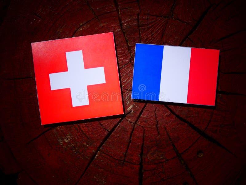 Drapeau suisse avec le drapeau français sur un tronçon d'arbre d'isolement images stock