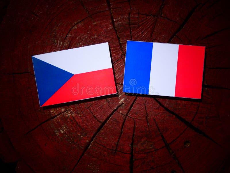 Drapeau tchèque avec le drapeau français sur un tronçon d'arbre d'isolement photographie stock