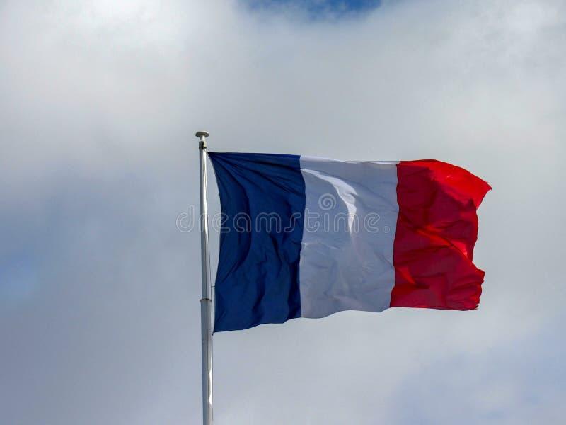 Drapeau tricolore profond et de portée de couleurs de tissu de la France flottant dans le vent photographie stock libre de droits