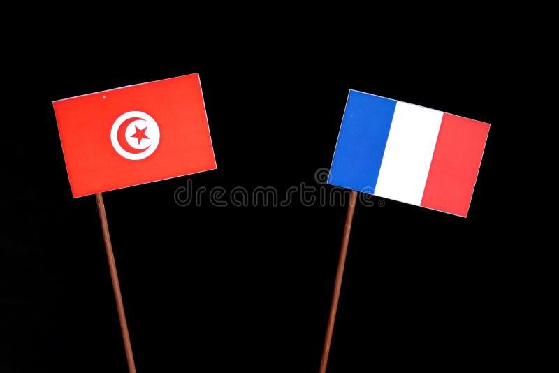Drapeau tunisien avec le drapeau français sur le noir image libre de droits
