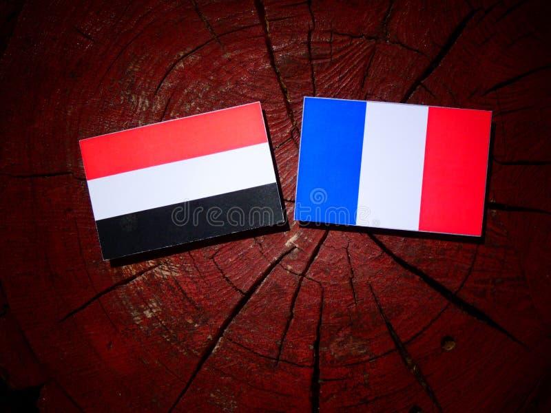 Drapeau yéménite avec le drapeau français sur un tronçon d'arbre d'isolement images stock