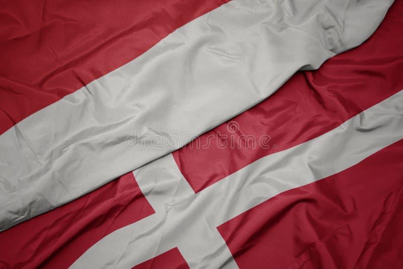 drapeaux colorés du danemark et drapeau national de l' indonésie photo libre de droits